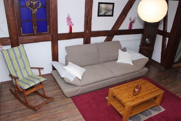Schaukelstuhl und Couch im Wohnzimmer der Ferienwohnung Lärche